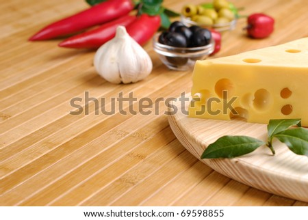 Emmental or maasdam cheese with vegetables on the table