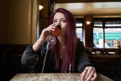Emo girl drinking alone in the pub and staring at camera