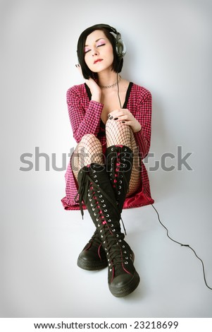stock photo : emo girl in headphones listen to music on gray background