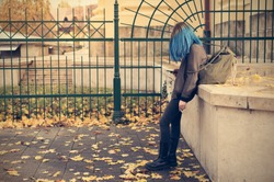Emo girl smoking and use her phone in the street. Young student with blue colorful dyed hair