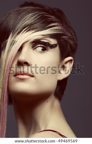 Emo girl with long blond fringe and cat eye make-up,  piercing on ear, lip