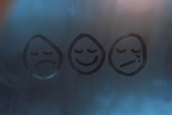 Emoji mood, condensation emoji painted on the window, good mood, bad and sad mood, smile and tears, sadness and happiness, painted heads with faces, winter time, drops on window,