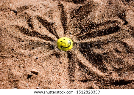 Emoticon with a smile in the sand with drawn little sun rays. The sun is out of the sand. The concept of summer, vacation, summer vacation