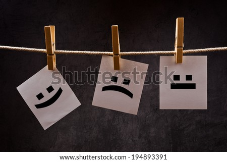 Emoticons printed on note paper attached to rope with clothes pins - happy, sad and neutral. - stock photo