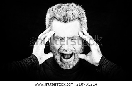 Emotion black and white portrait of man with close eyes on black background. (Photo has an intentional film grain)