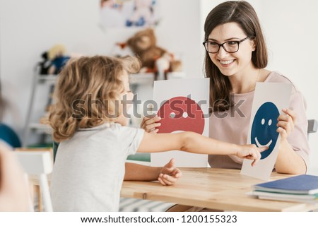 Emotion emoticons used by a psychologist during a therapy session with a child with an autism spectrum disorder. Foto stock ©