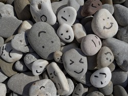 Emotion management concept, stones with painted faces symbolize different emotions. We are all different, but all together, learning to manage emotions