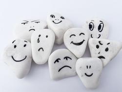 Emotion management concept, stones with painted faces symbolize different emotions. We are all different, but all together, learning to manage emotions. Soft background, white stones.