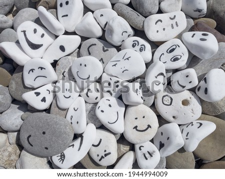 Emotion management concept, stones with painted faces symbolize different emotions. We are all different, but all together, learning to manage emotions. Emotional intelligence, role model. Сток-фото ©
