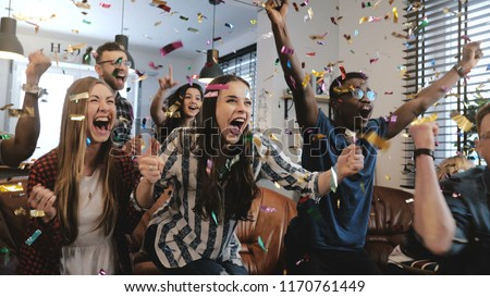 Emotion. Multi-ethnic fans celebrate winning. Confetti 4K slow motion. Passionate supporters shout watching game on TV.