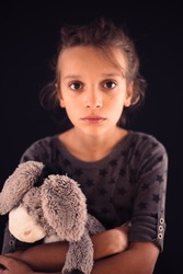 Emotion of sadness and lonelyness at face of teenage girl with blond hair and brown eyes keeping a toy in her hands