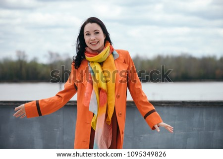 Emotion portrait of gorgeous dancing girl with black curly hair in orange cloak and varicolored bright scarf on background from river, trees and sky behind fence. Happy gaze of beautiful female eyes. #1095349826