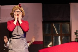 Emotional actress in a wig and red dress plays the comedic role of the housekeeper on the theater stage