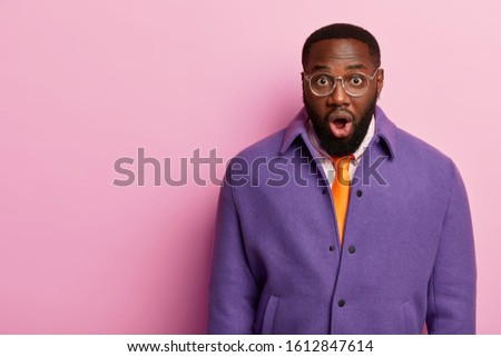 Emotional adult man with bugged eyes and opened mouth finds out shocking news, tries to realize what happened, stands alone, wears glasses, purple jacket, isolated over pastel rosy background