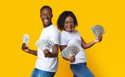 Emotional african-american couple dancing with bunch of money banknotes and celebrating success, yellow studio background. Joyful black man and woman won lottery, showing prize at camera and screaming