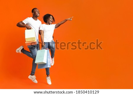 Emotional african-american couple with purchases jumping up and cheerfully pointing away at empty space, orange studio background. Happy young black man and woman aiming at advertisement