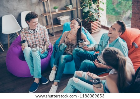 Emotional and glad youngsters sit in multi-colored armchairs with drinks in hands and loud laugh at the funny stories and comic jokes classmates sit in chair bag