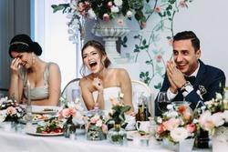 Emotional beautiful newlywed couple smiling at wedding reception