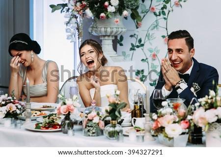 Emotional beautiful newlywed couple smiling at wedding reception #394327291