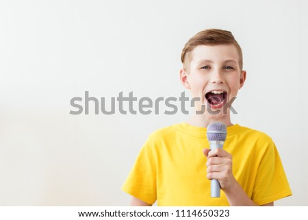 Emotional boy sings a song into the microphone with his mouth wide open. Copy space