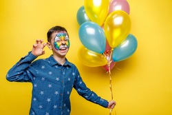 Emotional boy with aquagrim on birthday party, colorful tiger holding colorful balloons isolated on yellow background.