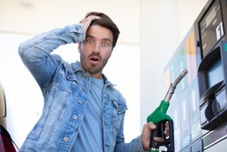 emotional businessman counting money with gasoline refueling car