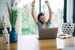 Emotional caucasian female freelancer enjoying online income from project overjoyed with successful business, smiling 20s woman celebrating completing learning course via laptop computer at home