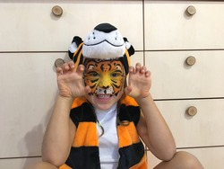 Emotional child with face painting of tiger mask bared his teeth on a wood background. On the head of a carnival hat with ears.