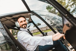 Emotional confident pilot sitting in the helicopter and smiling while opening the door of the cabin