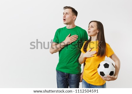 Emotional couple, woman man, football fans in yellow green t-shirt cheer up support team with soccer ball singing national country anthem isolated on white background. Sport leisure lifestyle concept
