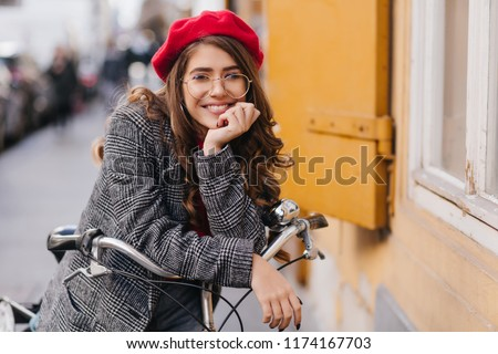 Emotional cute girl with curly hairstyle dreamy posing on bicycle. Charming young lady in coat enjoying active weekend in autumn.