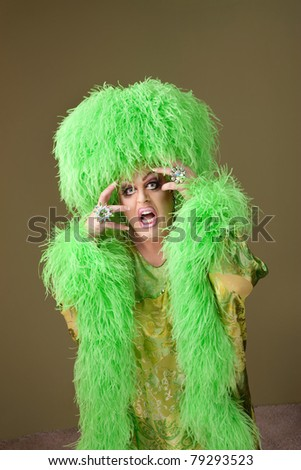 Emotional drag queen in boa and wig on green background
