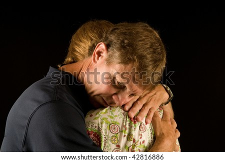 Emotional embrace - man (showing pained emotion) and woman hugging