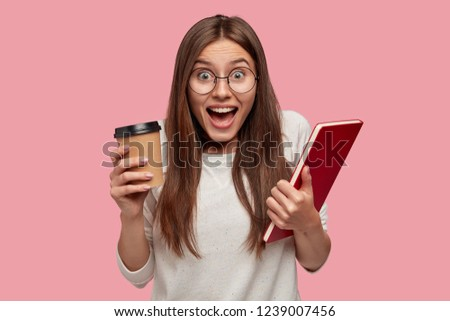 Emotional excited young lady with dark hair, shouts with happiness, carries takeaway coffee and book, dressed in white jumper, feels overjoyed, isolated over pink background. Emotions concept #1239007456