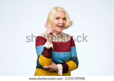 emotional expressive grandmother pointing with index finger up #1314729980