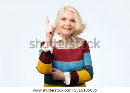 emotional expressive grandmother pointing with index finger up #1316185835