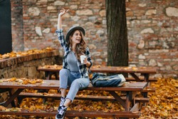 Emotional female model in short jeans and black shoes drinks coffee in park in warm september morning. Attractive caucasian lady looking away and waving hand in yard covering with yellow leaves.