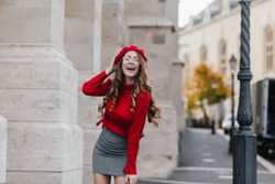 Emotional female model in soft red sweater posing in front of old white building. Portrait of graceful european girl with long curly hairstyle having fun during outdoor photoshoot.