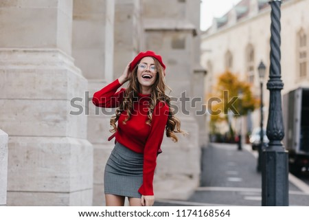 Emotional female model in soft red sweater posing in front of old white building. Portrait of graceful european girl with long curly hairstyle having fun during outdoor photoshoot. #1174168564