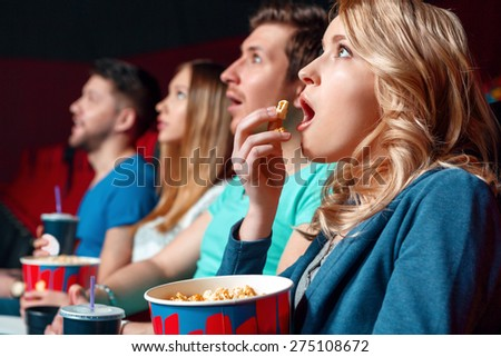 Emotional film. Excited blond woman eating popcorn emotionaly in cinema near other viewer.