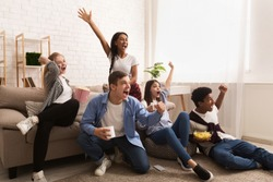 Emotional football fans. Teens watching match at home and celebrating victory, free space