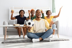 Emotional football fans young african american men and women watching game together at home, celebrating win of their team, raising hands up and screaming, excited black guy with soccer ball