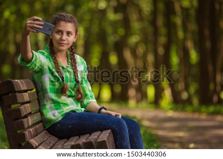 Emotional girl teenager with long hair hairstyle braids in a green shirt sits on a bench in the park.