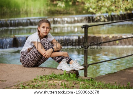 Emotional girl teenager with long hair hairstyle braids walks in the park at the waterfall like on a sunny day.