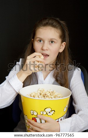 emotional girl with popcorn on a black background