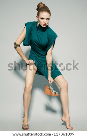 emotional gorgeous fashion model in green (blue) dress over gray background holding one shoe. studio shot