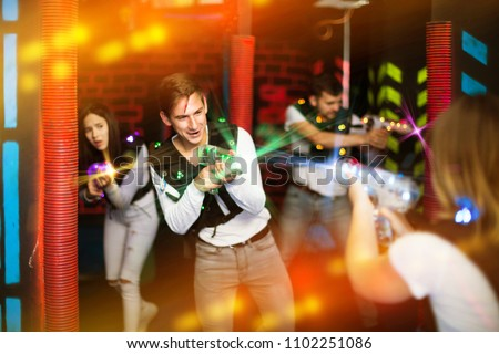 Emotional guy playing laser tag with friends on dark labyrinth in colorful beams of laser pistols  - Shutterstock ID 1102251086