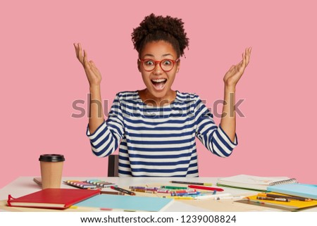 Emotional illustrator raises hands in eureka, exclaims with happiness, has nice idea for masterpiece, works at table with notepad, crayons, coffee, wears striped sweater, isolated over pink background