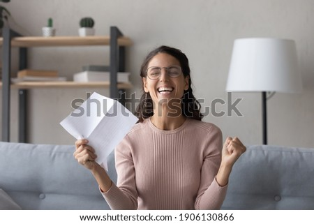 Emotional joyful millennial woman in glasses holding paper sheet in hands, getting dream job offer or university admission letter, celebrating professional success, reading loan approval notification. Photo stock ©