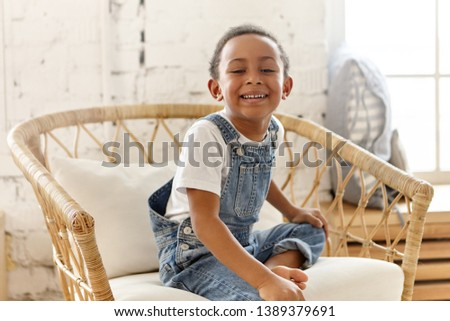 Emotional joyful toothy dark skinned little child sitting barefooted in woven armchair, smiling broadly at camera, showing white teeth. Joy, happiness, good mood, laughter and positive vibrations #1389379691